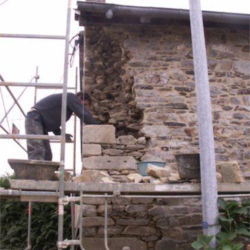 Hugo Gardrel maçon pierre reprend l'angle du mur en pierre/EIRL Terre Crue